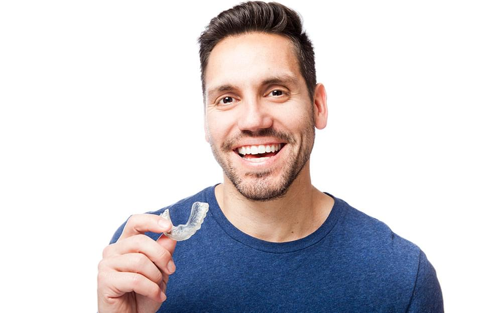man smiling with clear aligner